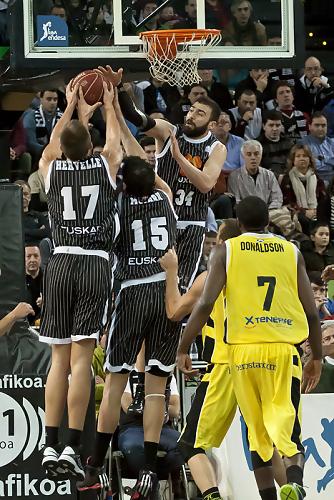 Tres jugadores del Bilbao Basket saltan a por el rebote (Foto: Luis Fernando Boo).