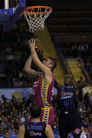 Paul Davis lanza bajo el aro ante Luis Flores y Germán Gabriel (ACB Photo / Tolo Parra)